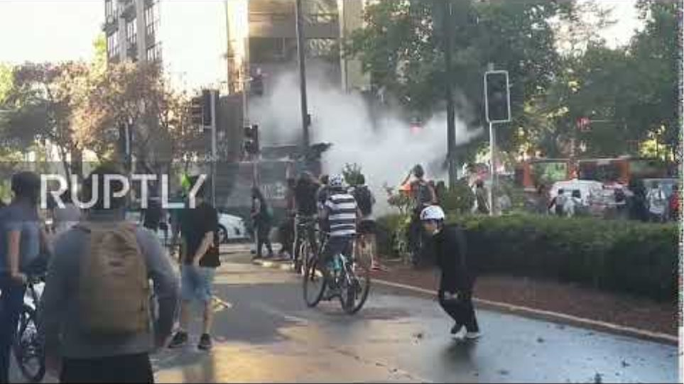 Chile: Demonstrator climbs on police truck and breaks water cannon